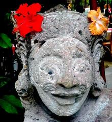 Hindu sculpture with Hibiscus flowers (Franc Le Blanc .) Tags: flowers bali sculpture lumix panasonic hibiscus hindu kuta bungasepatu lovelyflickr