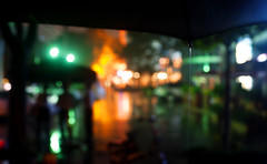 Umbrella 2 (Jonathan Kos-Read) Tags: china orange storm green wet water rain yellow night umbrella asia bokeh beijing raining sanlitun drizzle wetstreet nightrain pouringrain goldenratio 16181 underanumbrella bardistrict neonreflections