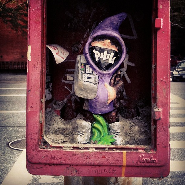 Street art gnome hiding in an old schools fireman's box