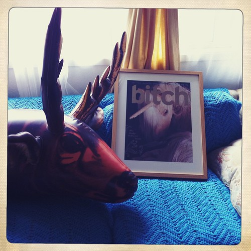 Make-Believe issue cover featuring a unicorn. The print sits on a couch on a blue blanket, and an inflatable moose/deer head sits next to it