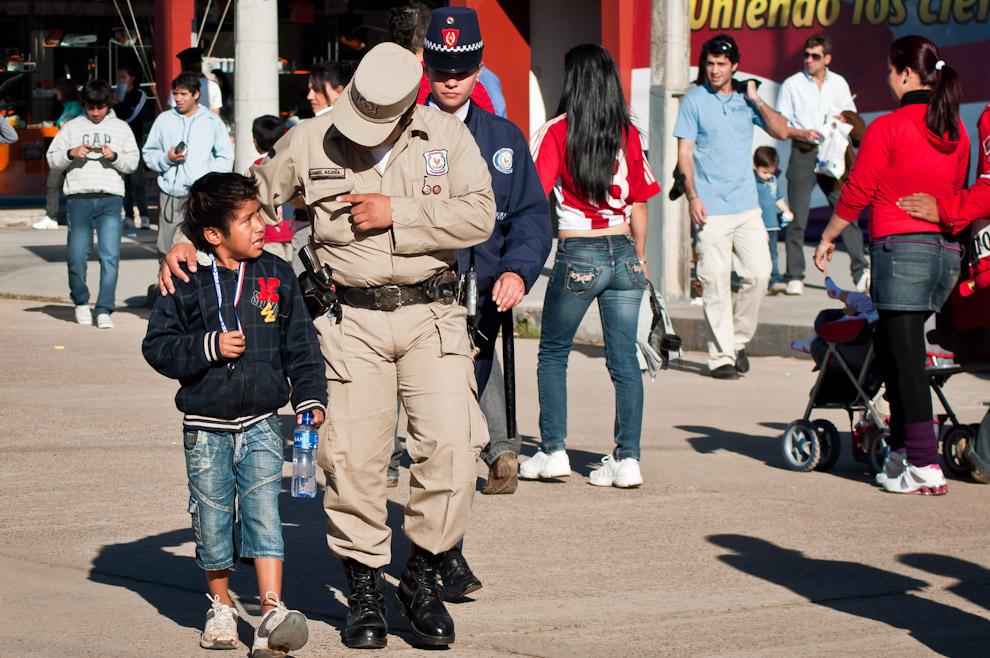 Un niño es acompañado por un policía hasta un puesto de seguridad para atenderlo. Unos 700 efectivos policiales velaron por la seguridad de los visitantes en cuanto a orden y prevención según informe del comisario principal Pablino Vera, jefe de Orden y Seguridad de Central. (Elton Núñez)