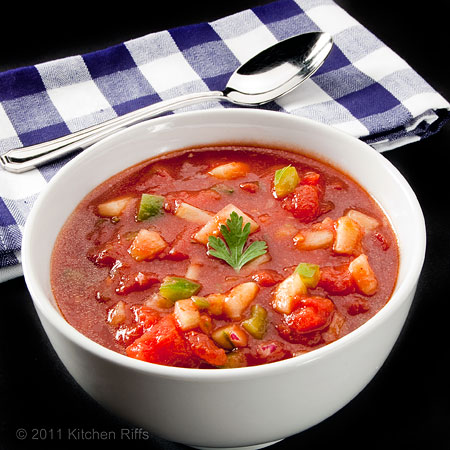 Gazpacho in white bowl with spoon and napkin, black background