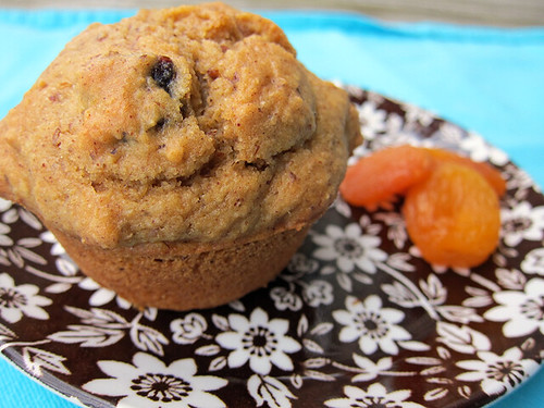 A muffin sits on a small plate alongside a pile of dried apricots.