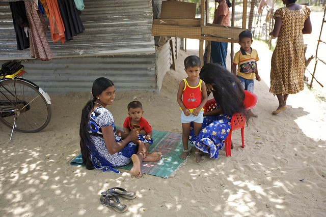 Children and young mothers by their home in the Muthur camp