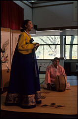 Performer and Puk Player at P'ansori Performance, Seattle (Washington State Folk Arts) Tags: drums musicalinstruments storytellers narrators puks verbalartsandliterature koreanpansoriperformers