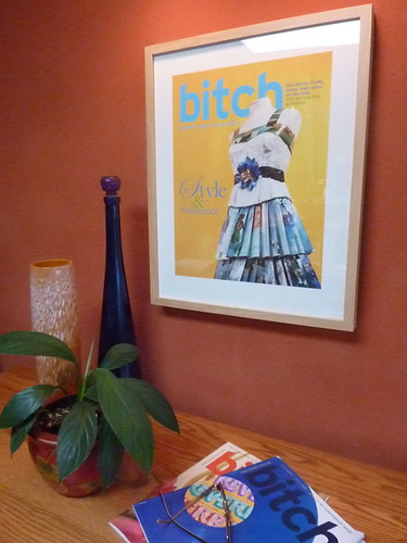 The yellow print of Style and Substance hanging on a red wall. A spread of Bitch magazines sit beneath it.