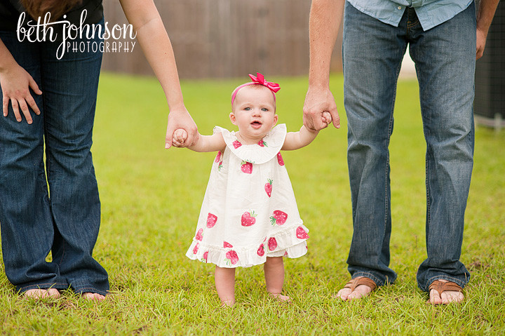 baby girl standing and holding mom and dad hands