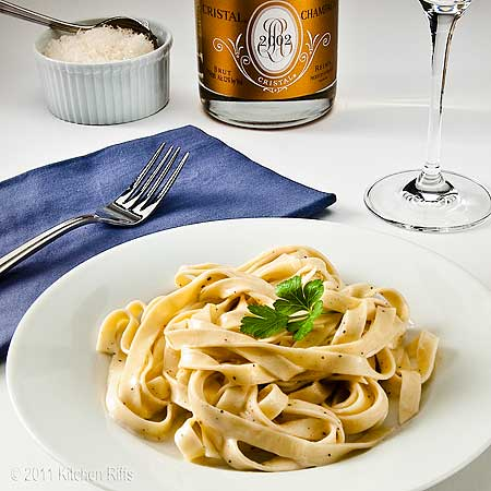 Fettuccine Alfredo on white plate with Champagne bottle and glass in background