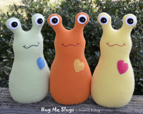 Light green, orange, and yellow Hug Me Slugs by Elizabeth Ruffing, original art toys
