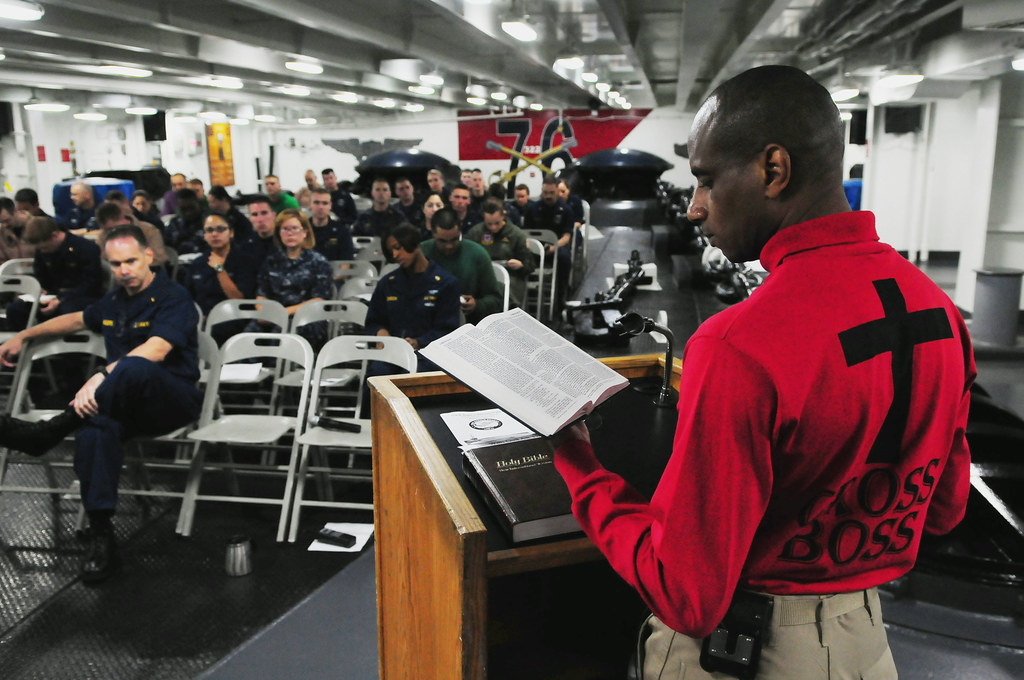 TN native/Navy chaplain leads Sailors and Marines in prayer during a contemporary Christian service in the forecastle of USS Ronald Reagan