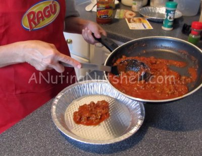 putting meat sauce in pie pan