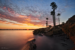 De Anza Cove (Lee Sie) Tags: ocean california blue trees sunset sea sky orange cliff beach water clouds bay coast seaside marine rocks pacific sandiego cove tide cement palm boulders coastal blocks pacificbeach