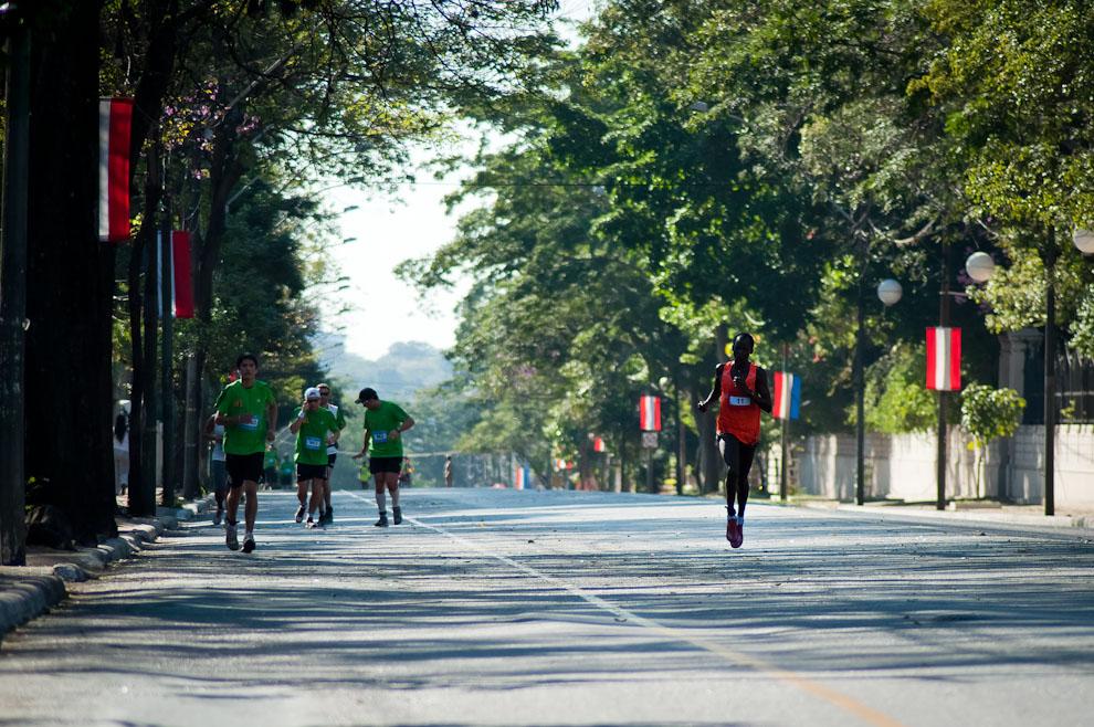 El keniano Christopher Kipyego (11), superior en su condición física, avanza sobre la avenida Mariscal López frente a Mburuvichá Róga. Christopher ocupó la segunda posición en la categoría principal de 42km con un tiempo de 02:23:47 (Elton Núñez)