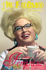 The F-Bomb feminine features the man from the masculine cover in his drag persona. She has big blonde hair, blue eyeshadow, glasses, big blue earrings, and is holding a coffee cup in both of her hands. She is wearing a nametag that says Sylvia.