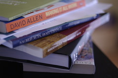 A curved stack of books including David Allen's Making It All Work.