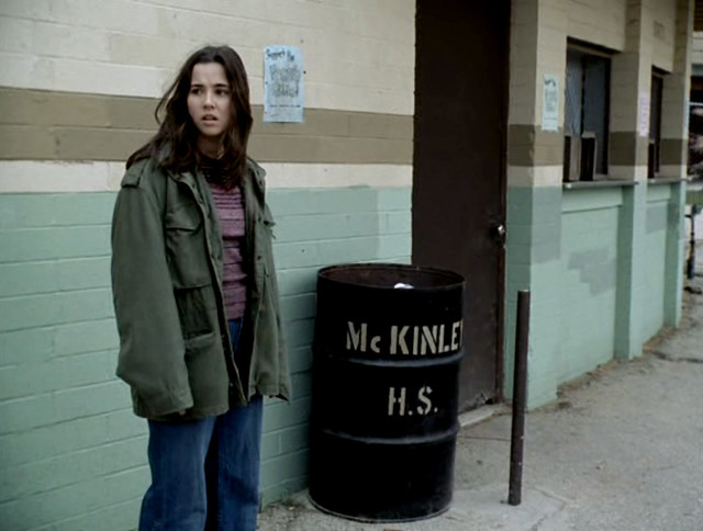 Lindsay Weir, a white teenage girl with dark hair, stands in front of a trash can that says McKinley HS on it