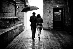 under my umbrella (Dennis_F) Tags: street italien light italy woman white man black wet rain zeiss umbrella walking couple day dof sony paar rainy tuscany mann pienza fullframe frau dslr schwarz centered 135mm toskana regenschirm weis strase 13518 a850 sonyalpha sonydslr vollformat cz135 zeiss135 dslra850 sonya850 sonyalpha850 alpha850 sony135 sonycz135 nowthatitsrainingmorethaneverknowthatwellstillhaveeachother