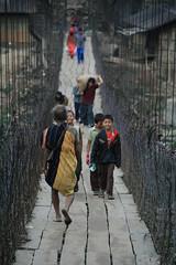 Aka tribesman crossing a foot bridge at Seppa on the way to the Kameng river Adventure rafting and Kayaking trip