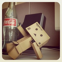 """Breakdancing Danbo says, """"Happy Monday!"""" (Chris Camargo) Tags: square toy robot bottle amazon dancing desk cardboard squareformat workspace barcode boxes cocacola tchotchke danbo earlybird amazoncojp iphoneography instagramapp uploaded:by=instagram foursquare:venue=4dd14364e4cd130e16aa0e81"""