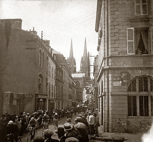 """This photo shows the peloton passing through the city of Quimper with its characteristic cathedral spires. The 210km 4th stage of the 1930 Tour started in Brest and finished in Vannes and was won by Omer Taverne (Belgium) in a time of 6h56'03"""". The Italian Learco Guerra continued leading the Tour until the 9th stage when Frenchman Andre Leducq took it in the Queens stage from Pau to Luchon. Photo: The Cycling History Collection"""