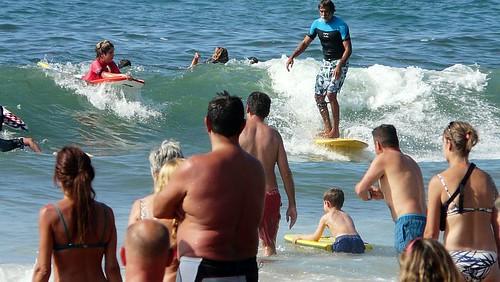 Mucha gente en la orilla y en el agua, en la playa de Sopelana. Surf