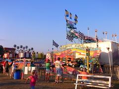 Carnival Midway. (dccradio) Tags: carnival sky festival mi bench fairgrounds ride michigan flag slide bluesky fair flags trucks hustl