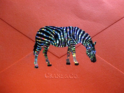 Sparkle zebra sticker on orange Crane envelope, close-up