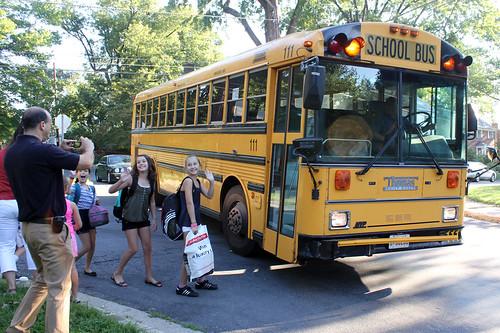 un groupe d'enfants prenant l'autobus scolaire sous l'oeil attendri de leur parents