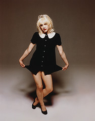 Courtney love curtsying in a black baby doll dress.