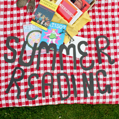 A photo of a red and white checkered picnic blanket lying on grass with a picnic basket and a pile of books on top of it. Cut-out letters are placed on top of the blanket, they spell out SUMMER READING