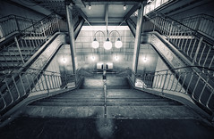 The Descent (Philipp Klinger Photography) Tags: light shadow urban bw white black paris france art industry lamp station metal stairs nikon frankreich europa europe industrial angle metro metallic cit mtro central wide perspective descent wideangle glossy artnouveau gloss railing nouveau fx deco metall philipp iledefrance ultra metalic cite descending ballustrade klinger ultrawideangle mtroparisien centralperspective zentralperspektive d700 mtrodeparis