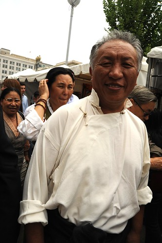 Grinning with happiness a Tibetan man in a traditional cream shirt, with women in chubas right behind him, tent market, Happy Birthday to His Holiness the Dalai Lama Parade, Kalachakra for World Peace, Washington D.C., USA by Wonderlane