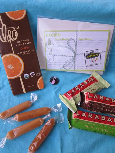 "Photograph of a set of recipe cards, an organic, fair-trade orange dark chocolate bar, a small pin with an elephant holding an umbrella that says ""Herbivore,"" three Larabars, and four Cocomels."