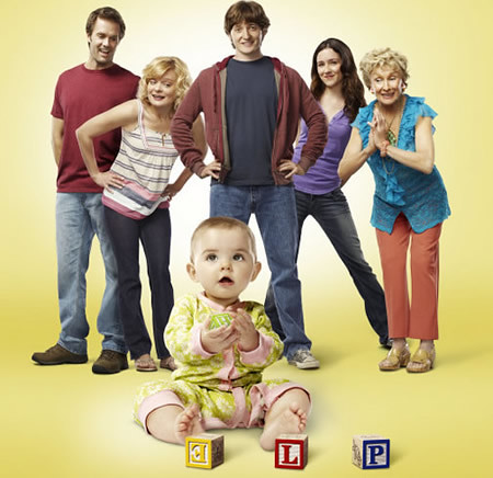 cast of the show Raising Hope. A young baby is in the foreground and five adults stand behind her. All are white.