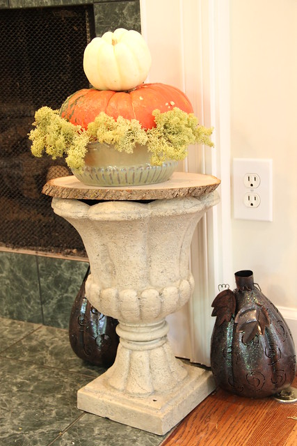 stacked pumpkins on urn with reindeer moss