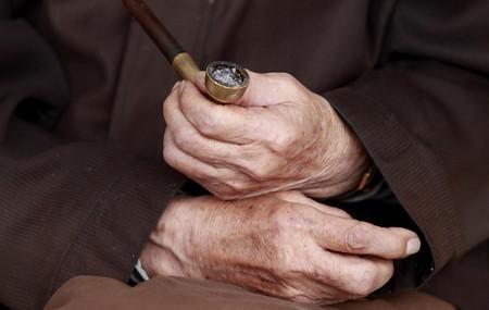 林生茂坐在路边的破沙发上手中拽着烟斗