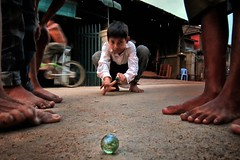 Steung Meanchey, Phnom Penh - Child play. The marble game. (Mio Cade) Tags: poverty camera boy game feet canon foot kid cambodia play prayer marble scholarship sponsor phnom compact ngo penh steung meanchey
