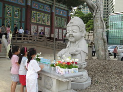 little girls bowing in front of baby Buddha