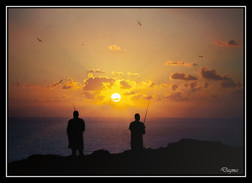 Sun between two fishermen..Calpe..Spain