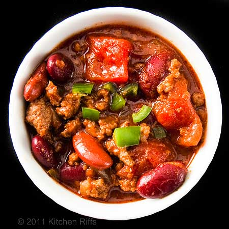 chili in white ramekin, overhead shot, black background