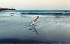 The lonely chair (Pablo  Ronald) Tags: light sea espaa seascape luz beach water landscape mar spain chair agua huelva playa paisaje arena reflect silla reflejo olas seda orilla ayamonte escena espign puntadelmoral abigfave colorphotoaward pabloronald