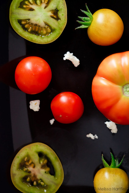 Red green and orange tomatoes on a black plate with feta cheese