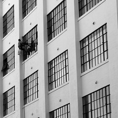 Descend (Dialed-in!) Tags: city windows urban bw white man black reflection lines vertical oregon portland person bucket downtown or working frombelow lookingup diagonal crop squareformat repetition pdx cleaner windowwasher job descending 500x500 bigmomma flickrchallengegroup flickrchallengewinner thechallengefactory