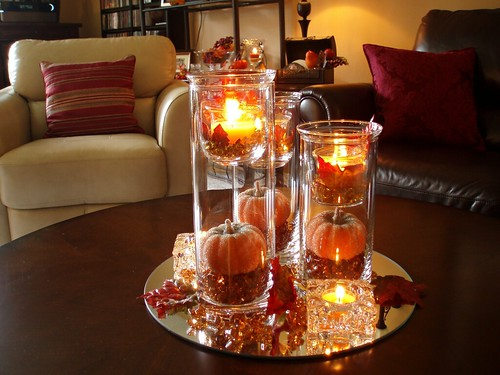 A fall centerpiece for the coffee table is created from three cylinder vases