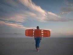 Orange Flight (Magic Pea) Tags: orange usa man mountains clouds america photography photo wings desert nevada flight dust magicpea