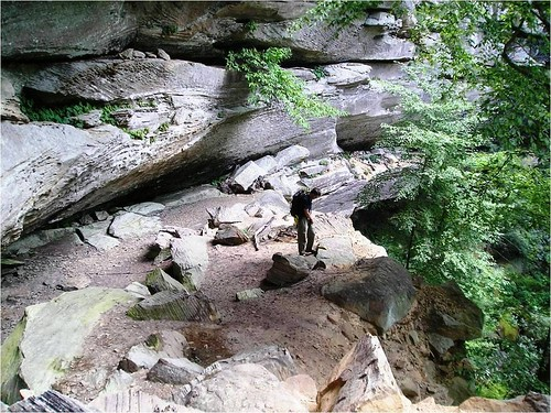 A hiker explores a rock shelter in the Red River Gorge (photo courtesy of Daniel Boone National Forest).