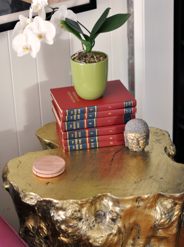 gold tree stump side table with vintage encyclopedias - orchids - buddha