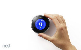 Hand adjusting a blue Nest Learning Thermostat