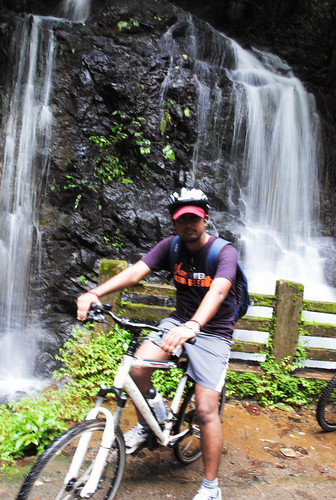 Sathya posing at a waterfall