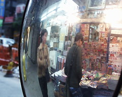 Magazine stall and mirror (Joybot) Tags: china street 2001 two people hk woman news man reflection glass shop digital shopping magazine person hongkong stand newspaper couple asia looking pair stall pedestrian olympus convex reflect newsstand vendor asie persons 中国 香港 passerby chine browsing 中國 browse domed earlydigital 亞洲 c1000l c100l